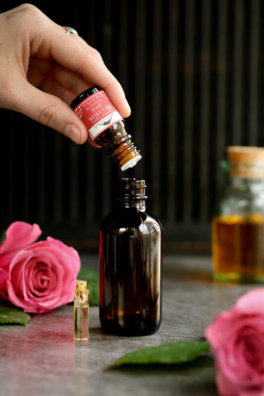 Blending a passionate massage oil with Bulgarian rose essential oil and organic jojoba oil in a glass container for massages and skin care.