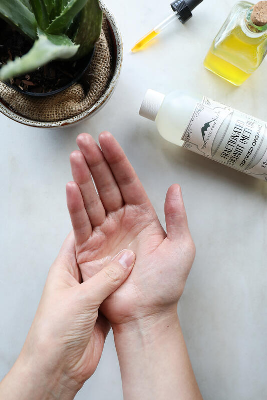 Hands applying oil to skin with a full bottle of fractionated coconut oil and plant in background.