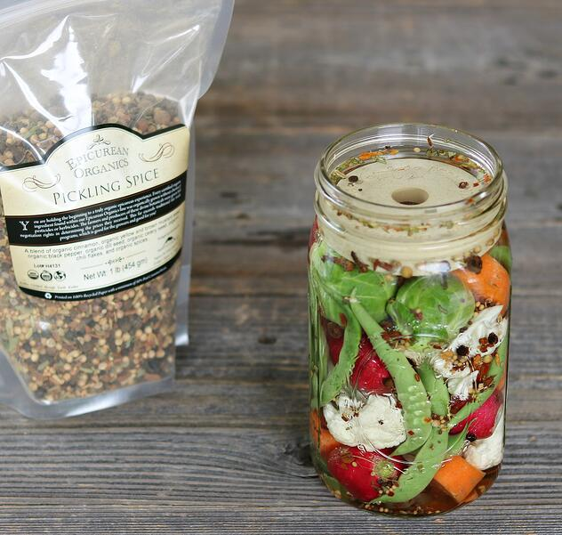 Mason jar filled with fermented veggies and pickling spice and Mountain Rose Herbs pickling spice