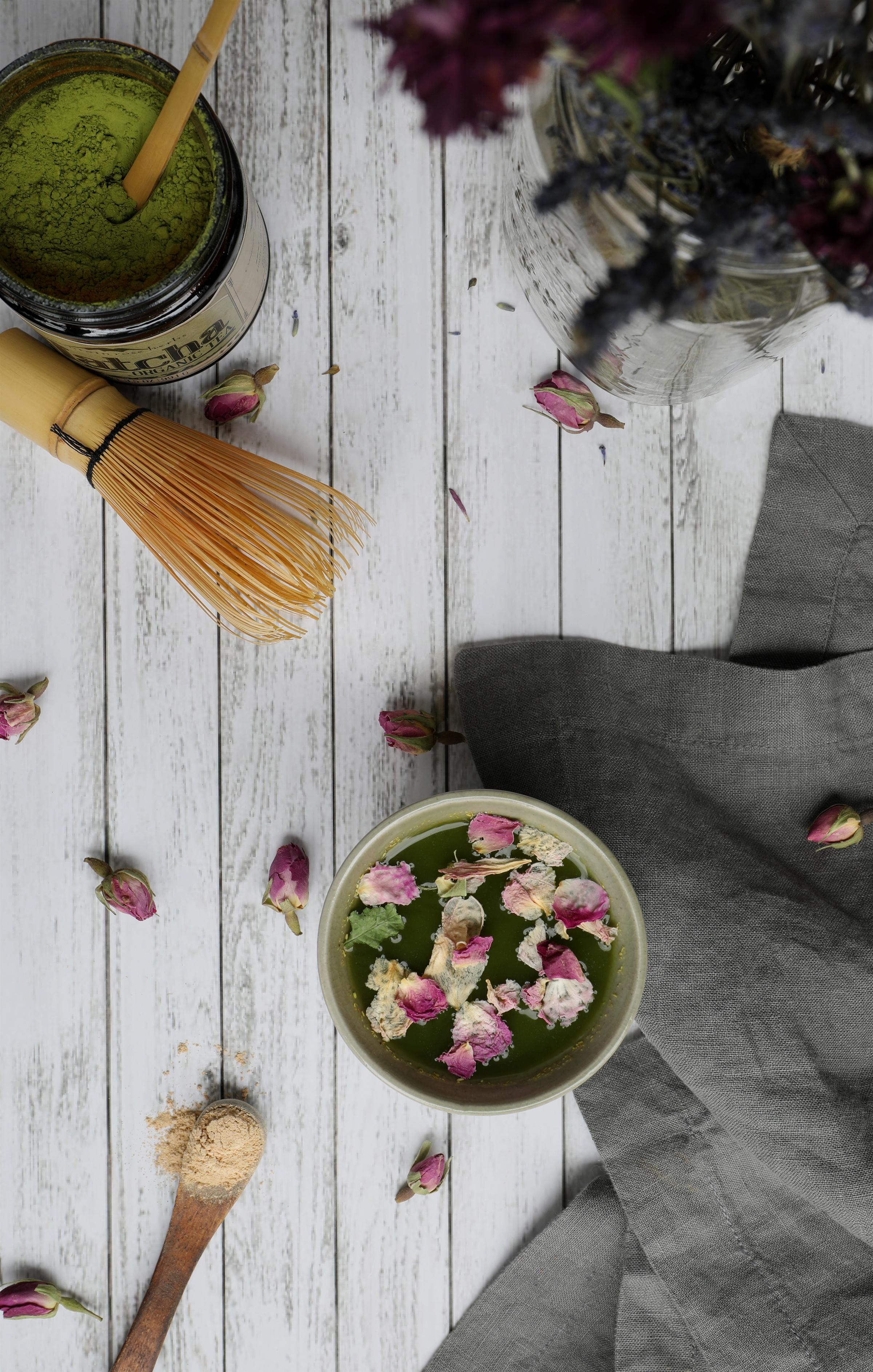 Mug with Matcha Tea and rose petals with tea accessories and cloth