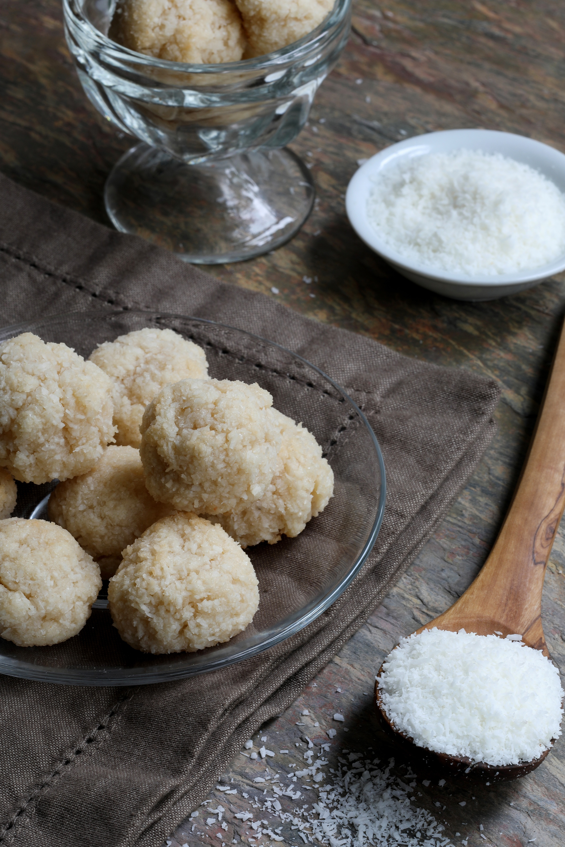 Organic coconut macaroon cookie balls on wood table with spoonful of coconut flakes
