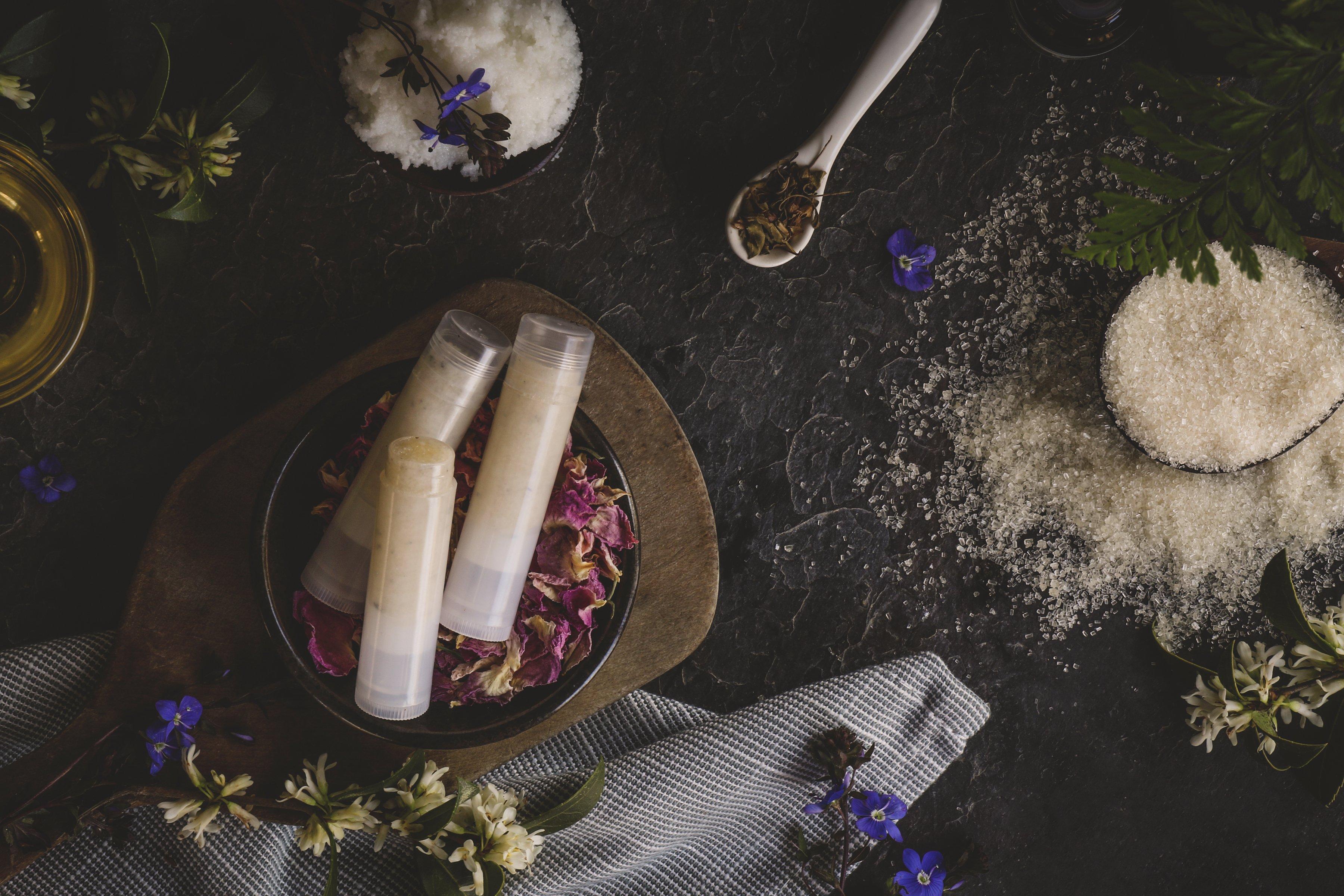 Display of lip balm tubes, salts, DIY ingredients and small purple flowers.