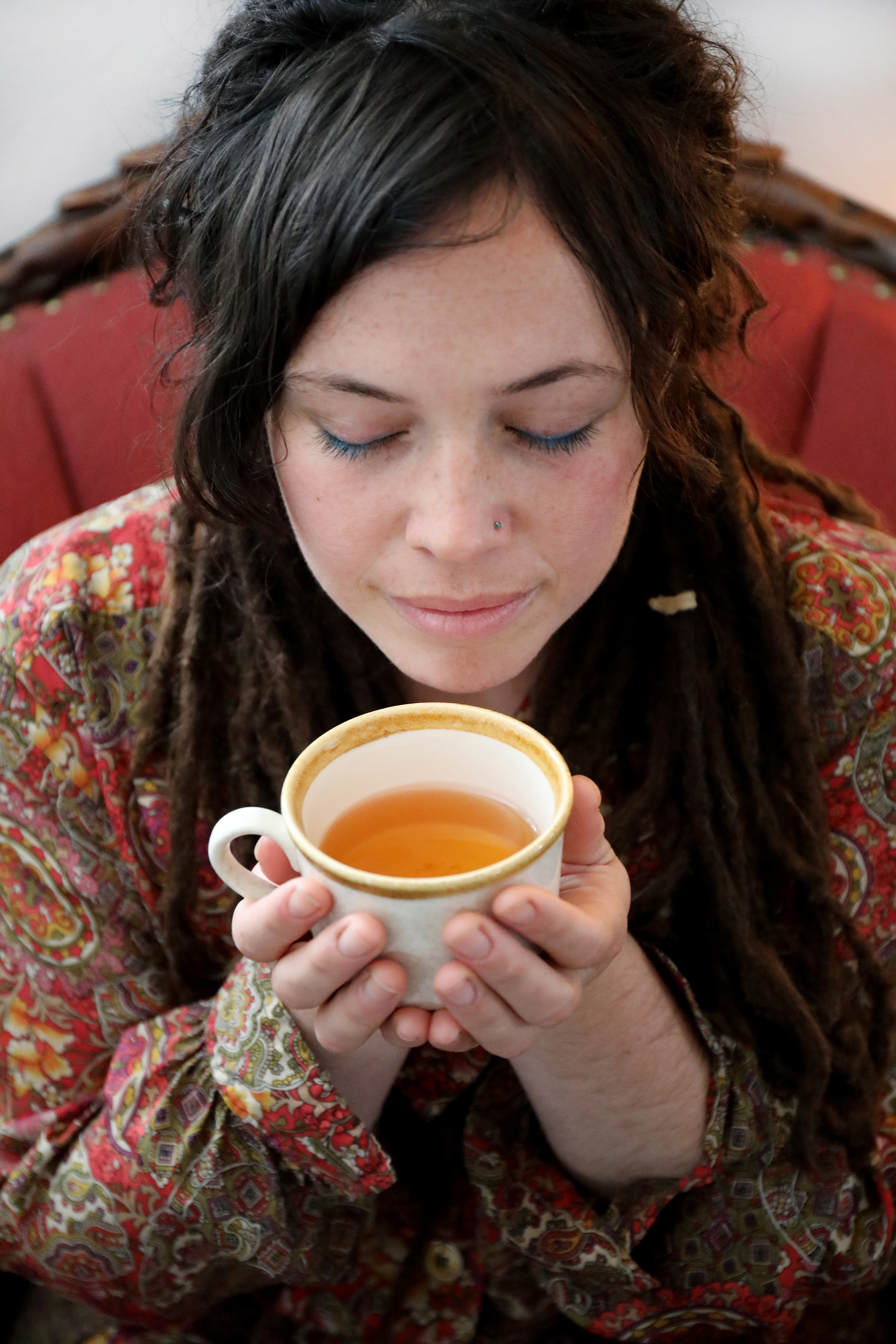 Young woman in paisley print dress holding cup of tea close to face to smell aroma