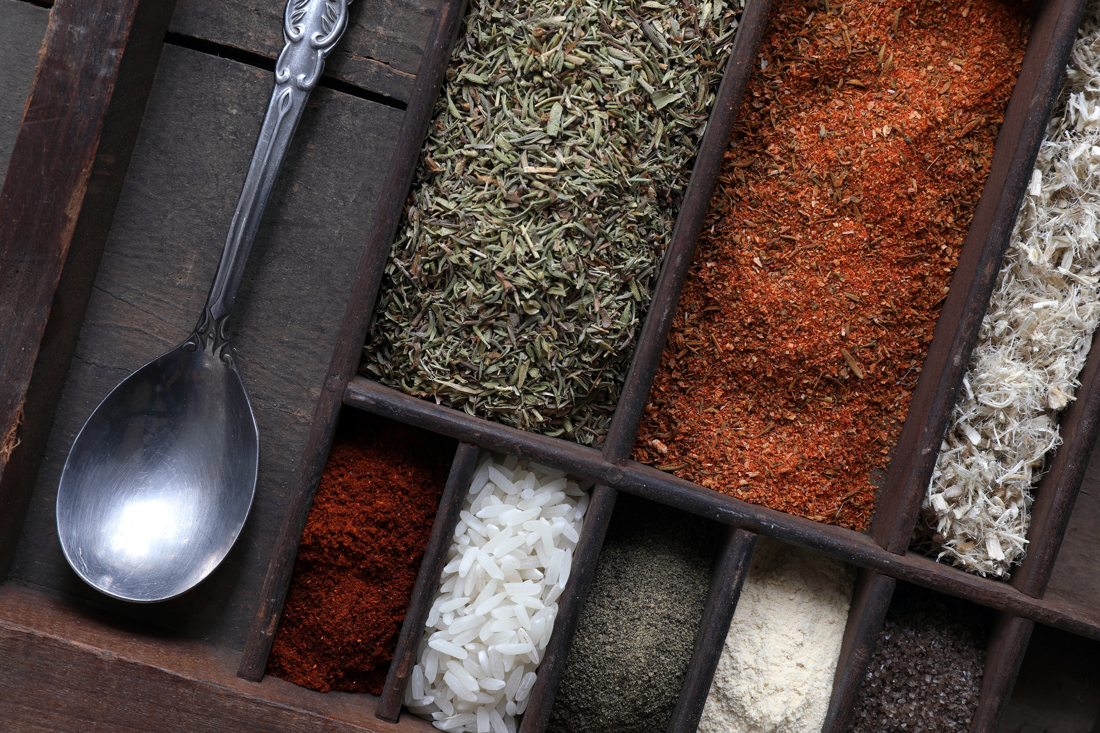 Spices and Ingredients used to make gumbo sitting in organizer with spoon