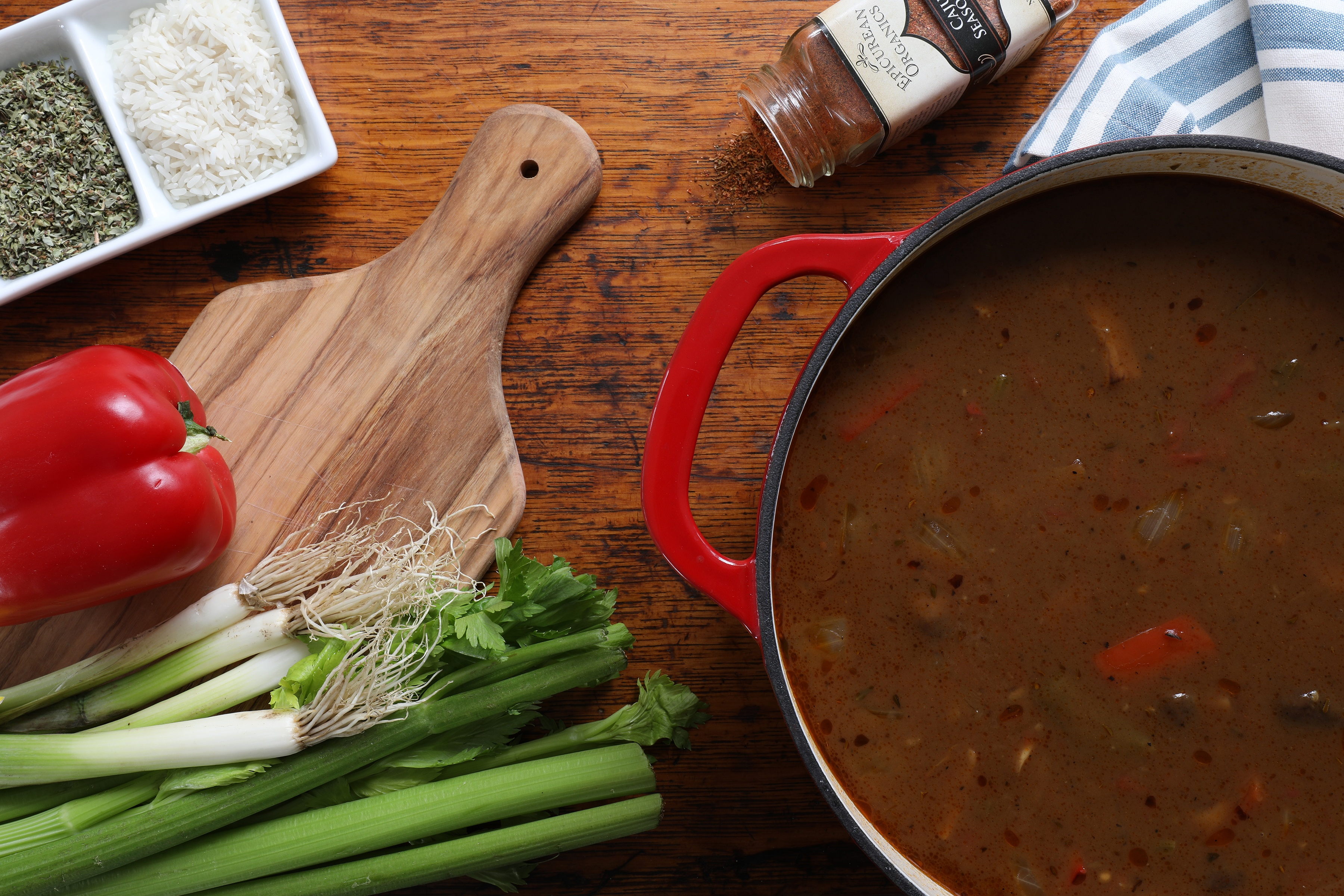 Vegetarian gumbo in pot with ingredients nearby on cutting board and spices and herbs nearby