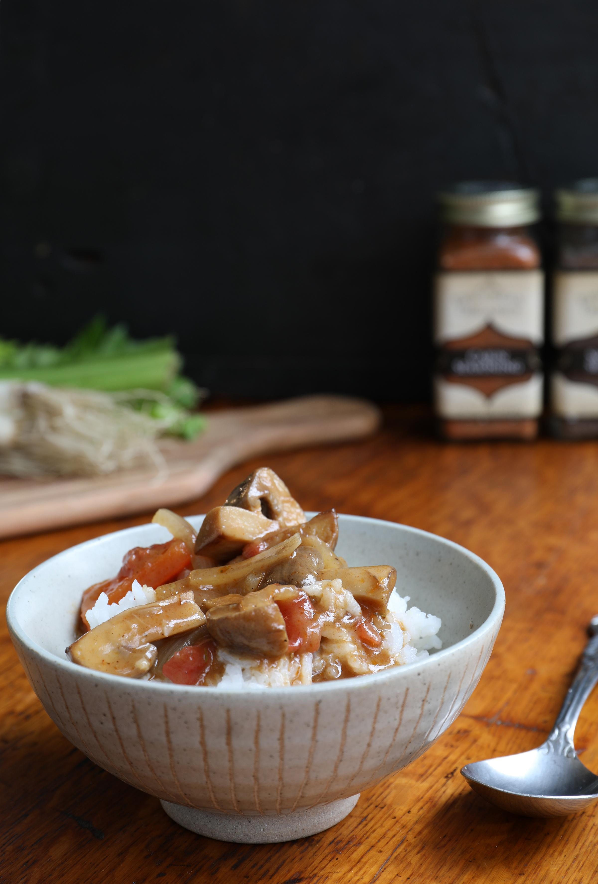 Vegetarian gumbo in bowl on top of rice sitting on wood countertop near cutting board