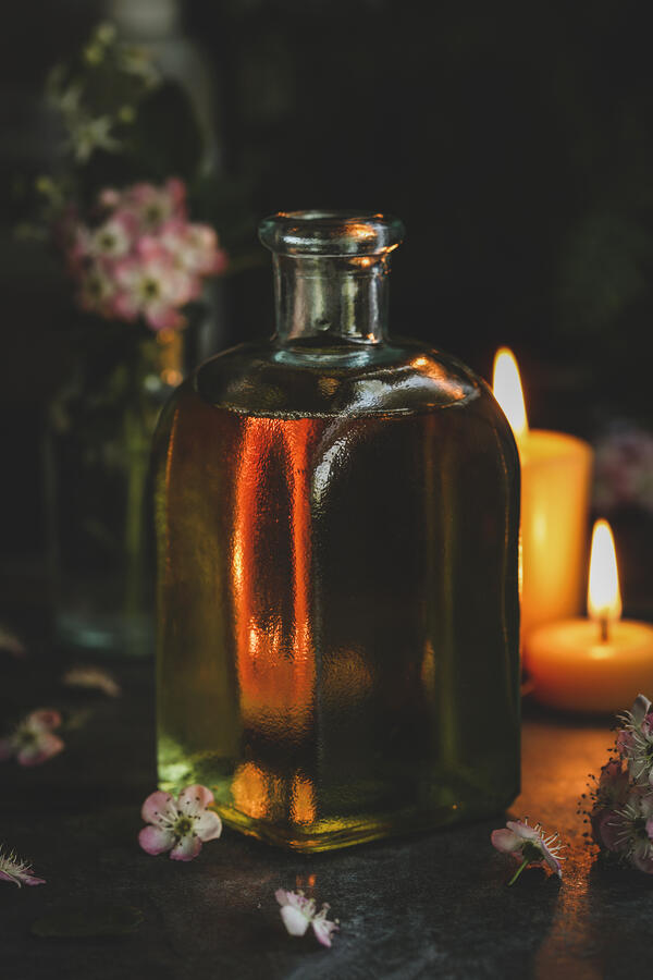 Square glass jar with massage oil- moody candles lit in the background.