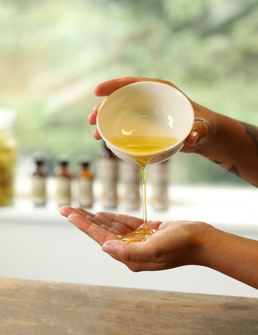 Golden massage oil is poured from a bowl to begin a relaxing massage. Several bottles of massage oils are arranged on a windowsill.