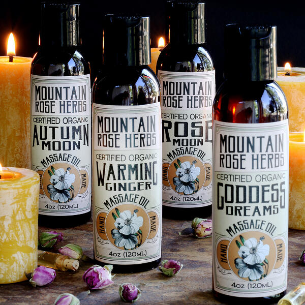 Natural and organic massage oil collection arrange with beeswax candles and dried rose buds. Four natural massage oil varieties from Mountain Rose Herbs.