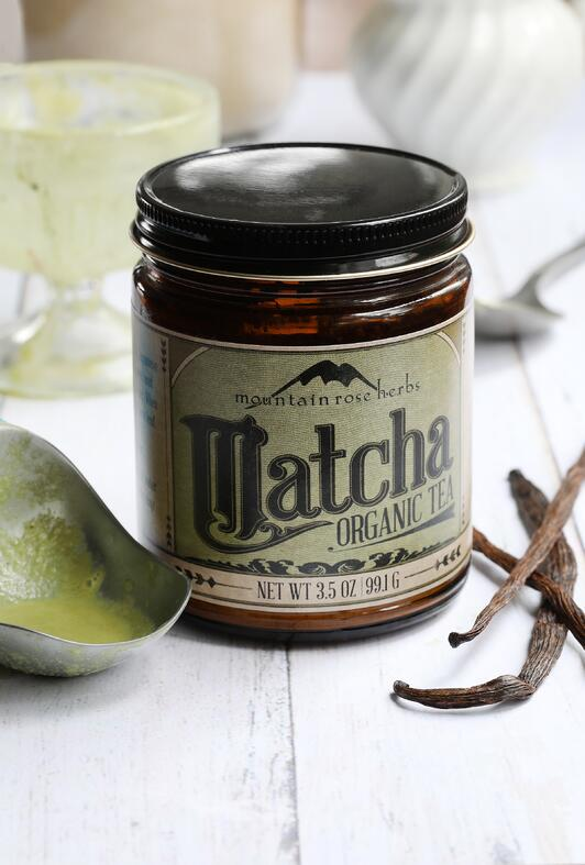 Jar of Mountain Rose Herbs Matcha powder laying next to vanilla beans