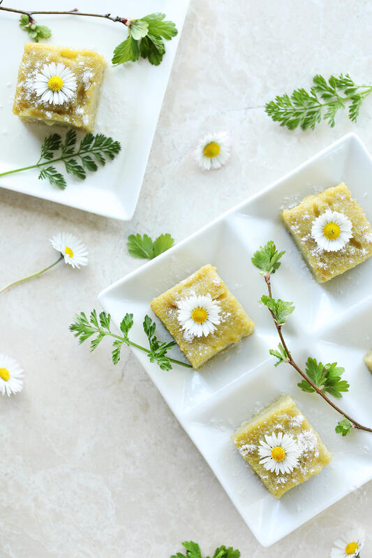Peppermint matcha mochi squares are made in a traditional Hawaiian style called butter mochi, and is more like a fluffy cake than traditional Japanese mochi. Garnished with fresh flowers and dusted with powdered sugar.