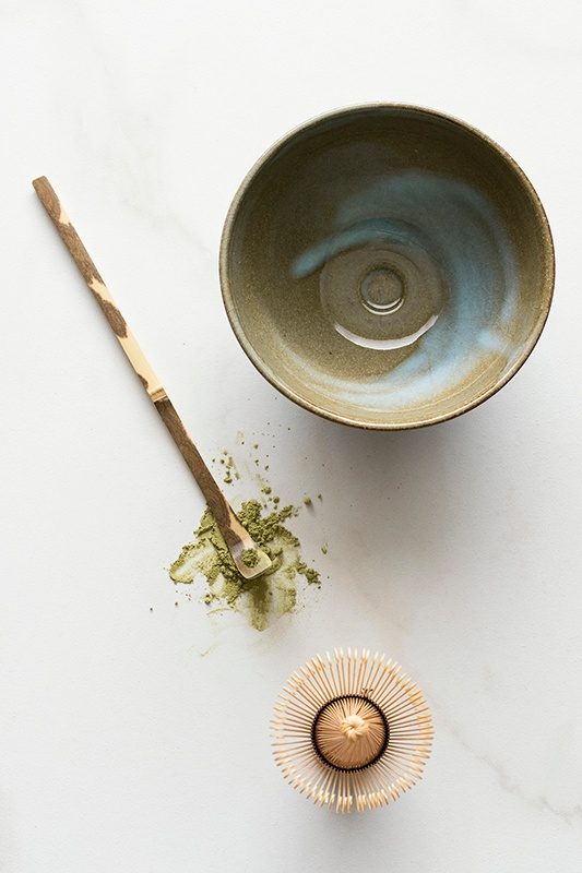 Ceramic bowl with matcha tea and whisk