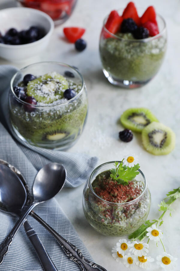 Clear cups of organic matcha chia pudding are garnished with fresh fruits and freshly picked feverfew flowers. Kiwis, blackberries, strawberries, and blueberries adorn the cups of green matcha chia pudding.