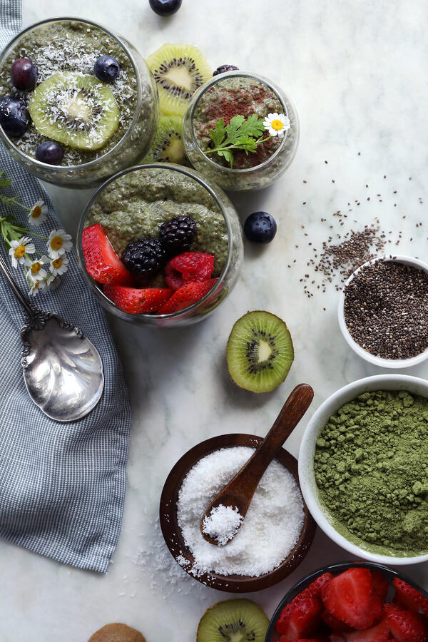 Ingredients are assembled to make matcha chia pudding. Organic coconut flakes, chia seeds, and matcha powder, along with fresh fruits and completed glasses of matcha chia pudding.