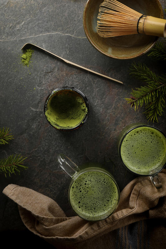 Frothy cups of matcha green tea are prepared using a bamboo matcha whisk and bamboo matcha spoon.