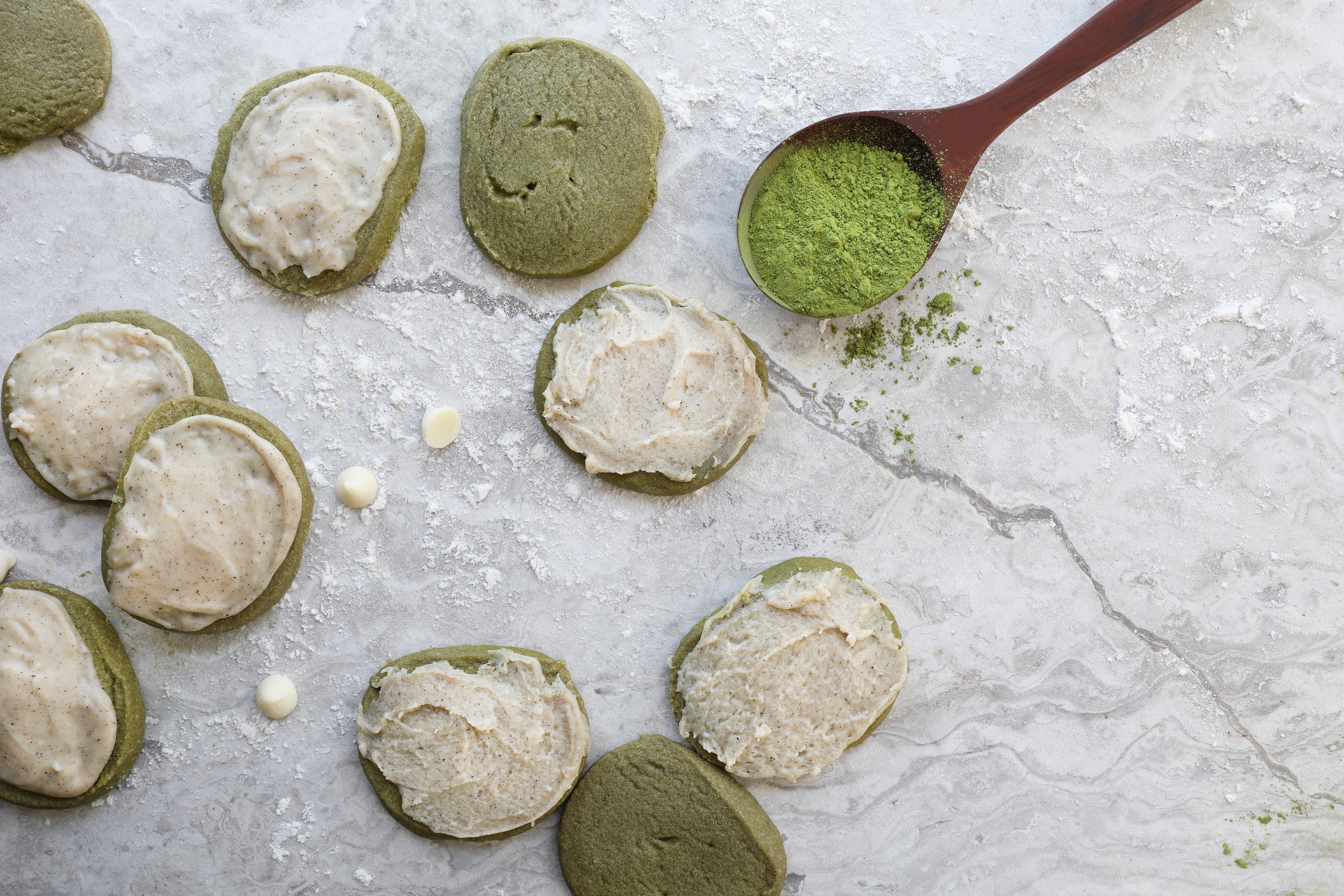 Matcha shortbread cookies sitting on granite counter with spoon of matcha powder and white chocolate chips