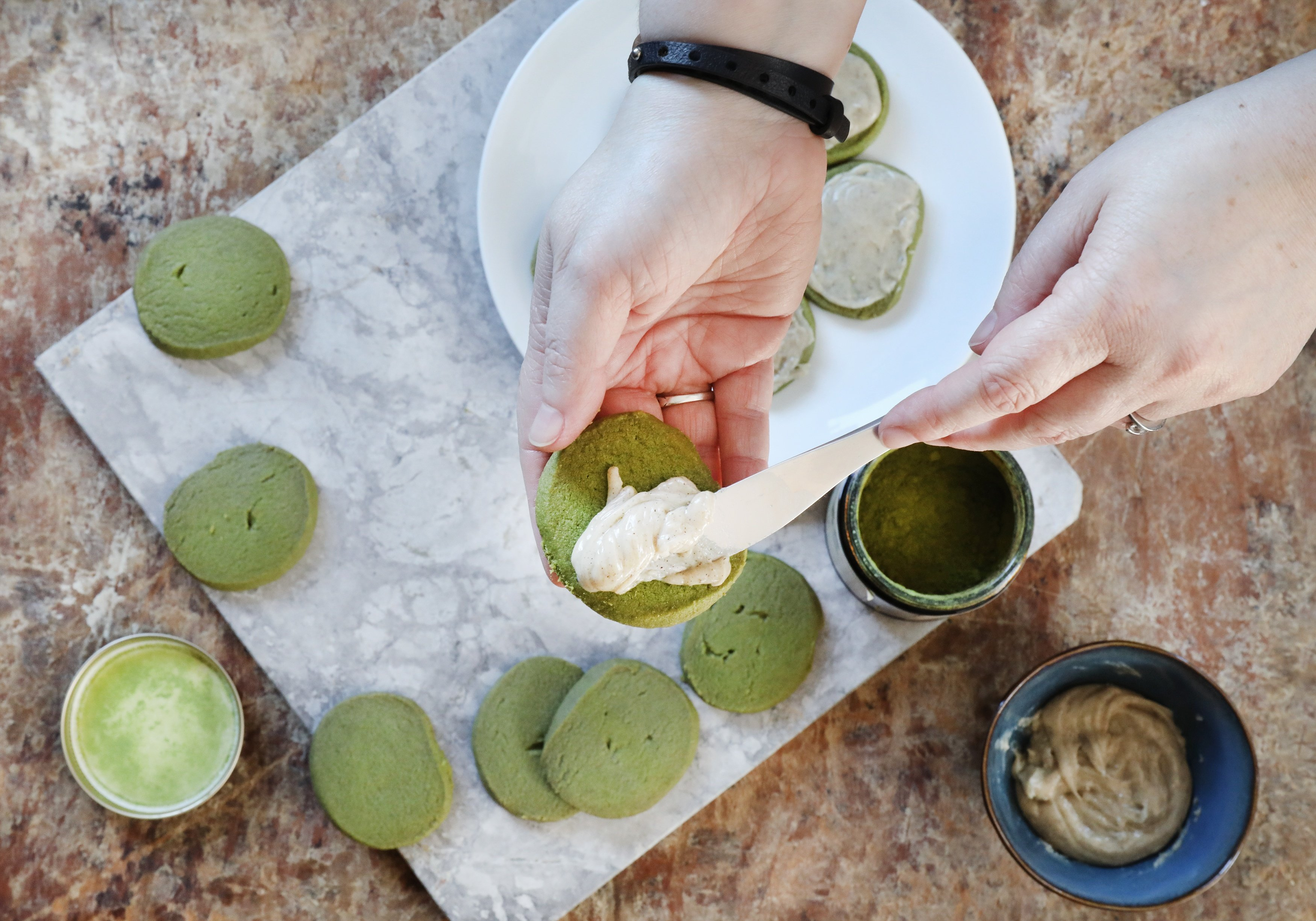 Hand with butter knife spreading vanilla bean glaze on shortbread matcha cookies