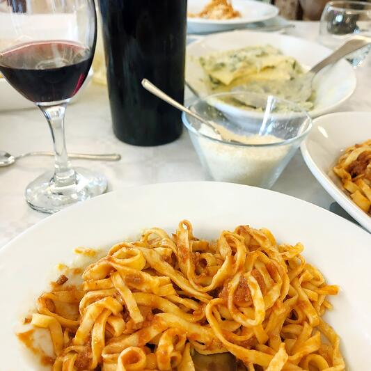 Table set with homemade Italian style meal, pasta with red sauce, glass of red wine, parmesean cheese.