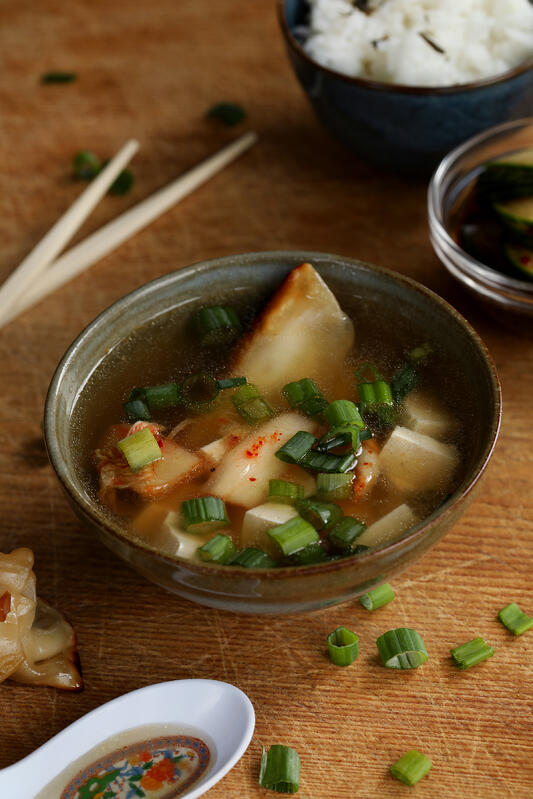 Miso soup is garnished with potstickers, tofu, green onions, and kimchi for a delicious and healthy appetizer or meal.
