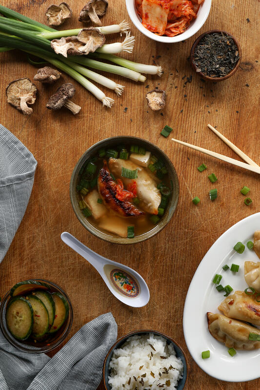 A restaurant-ready bowl of miso soup is served with side dishes like kimchi, potstickers, and cucumber salad. Filled with tofu and other treats, miso soup is an excellent meal starter.
