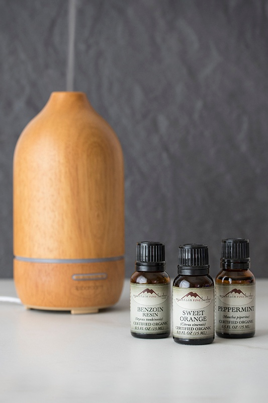 Bottles of essential oils next to a wooden diffuser