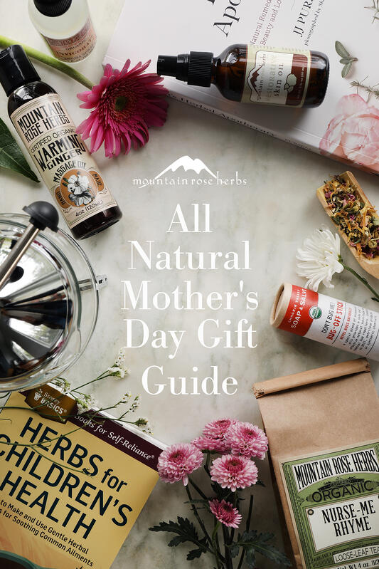 Pinterest pin for All Natural Mother's Day Gift Guide. Many mother's day gifts arranged on a marble counter top with flowers.