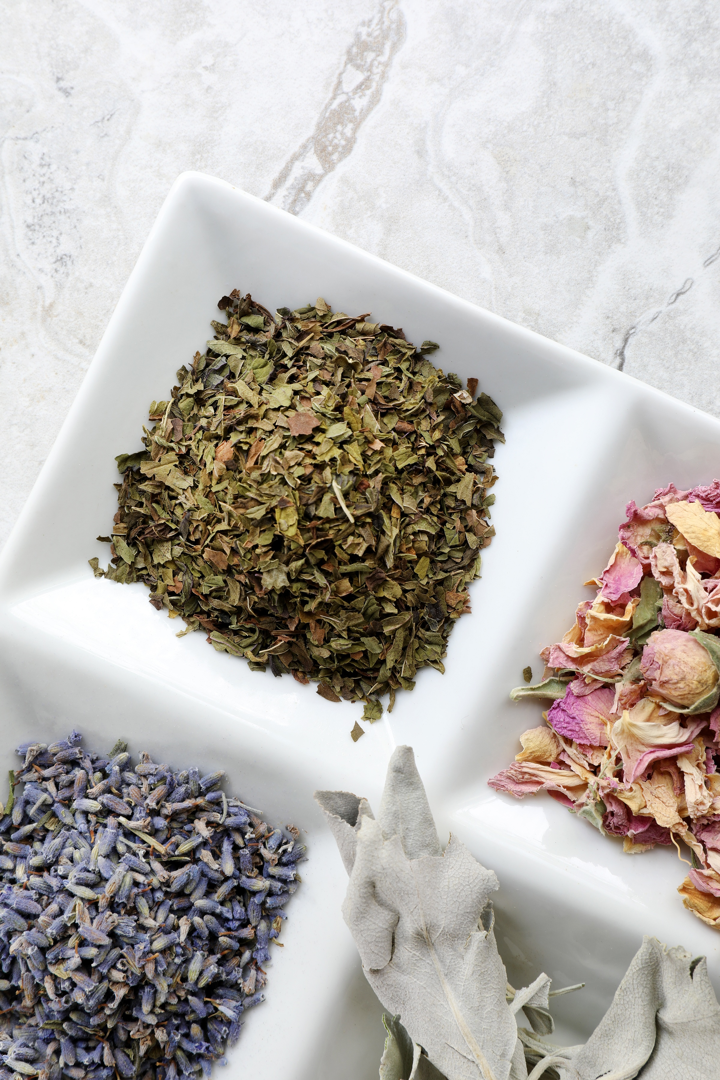 Dried herbs including lavender flowers and rose buds in divided white porcelain container on marble counter