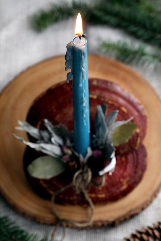 Candle burning on top of reishi mushroom centerpiece with botanical accents