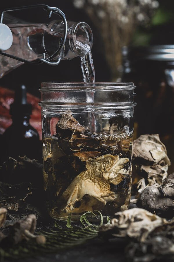 Dried mushrooms and a jar of alcohol in preparation for a mushroom double extraction.