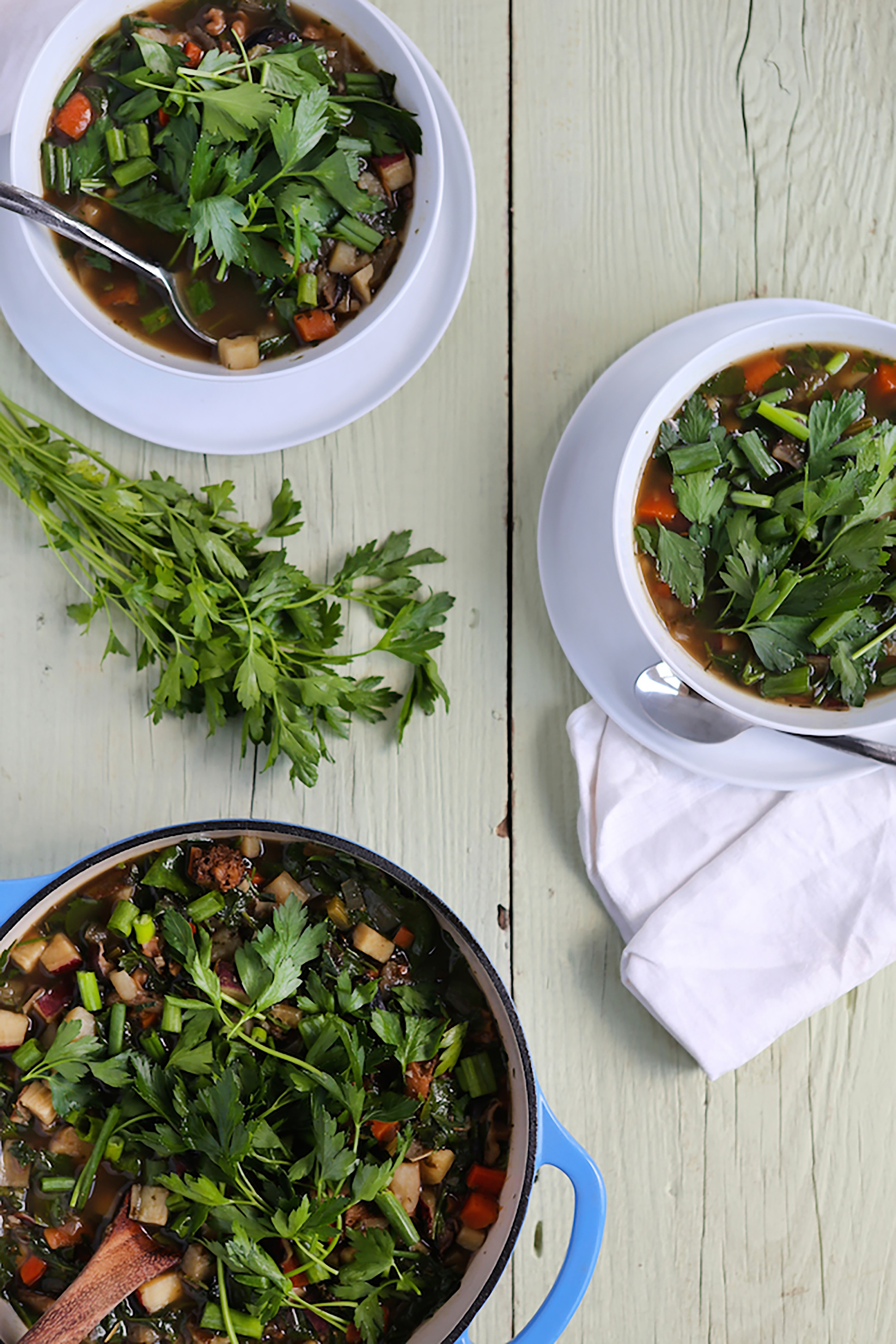 Bowls filled with mushroom tonic soup and topped with cilantro
