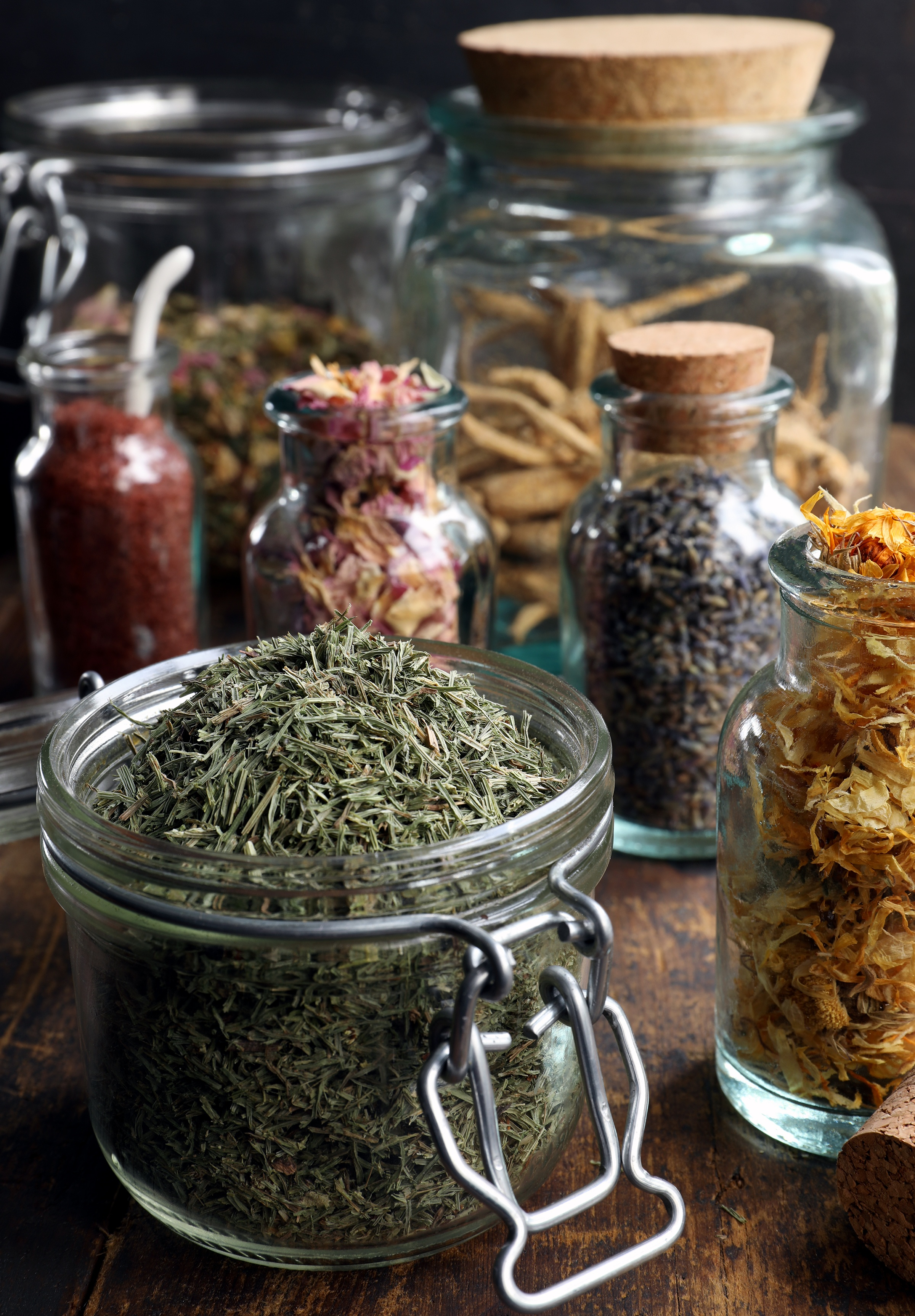 Glass pantry jars with bulk herbs and spices in them