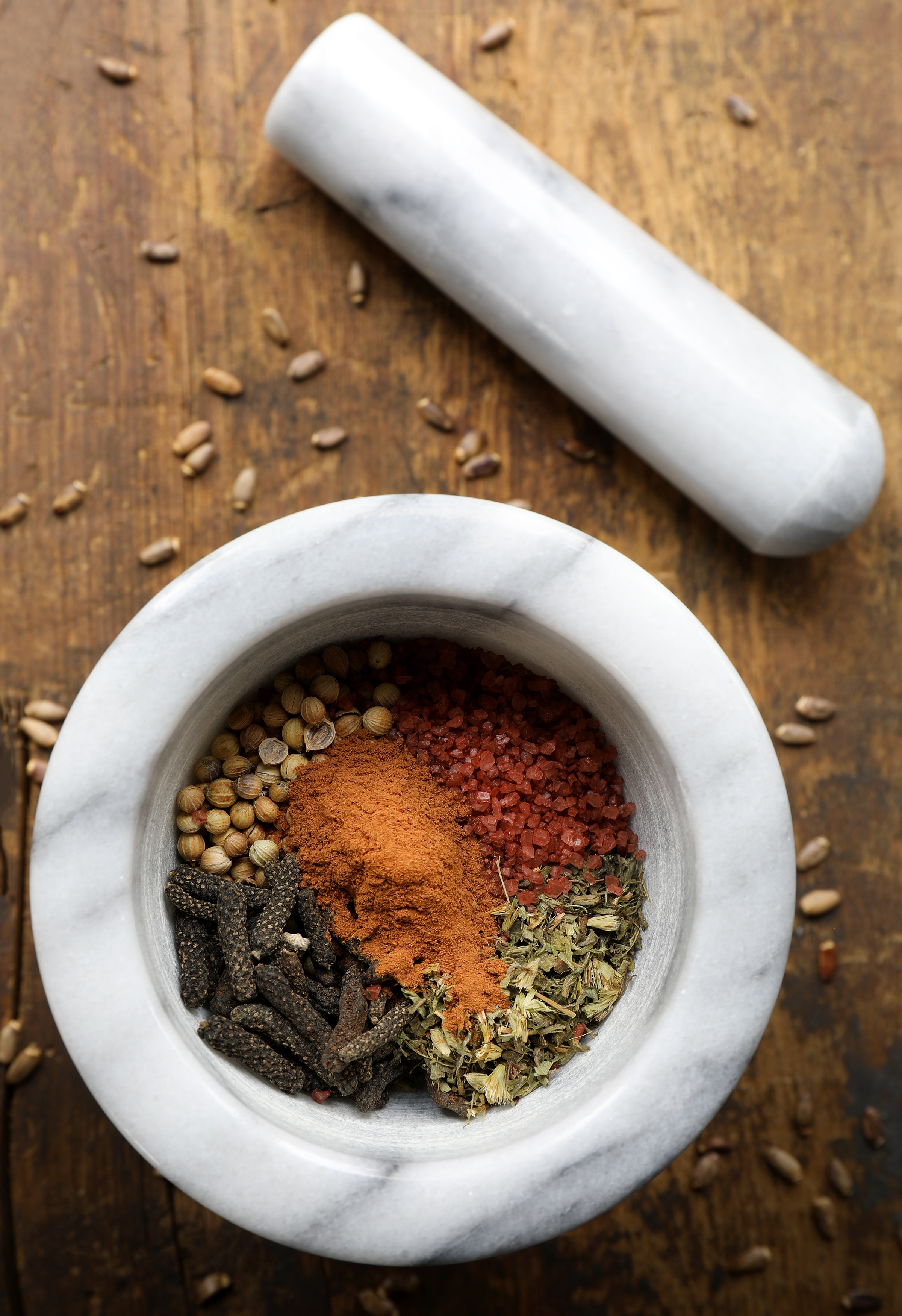 Whole dried herbs in mortar with pestle