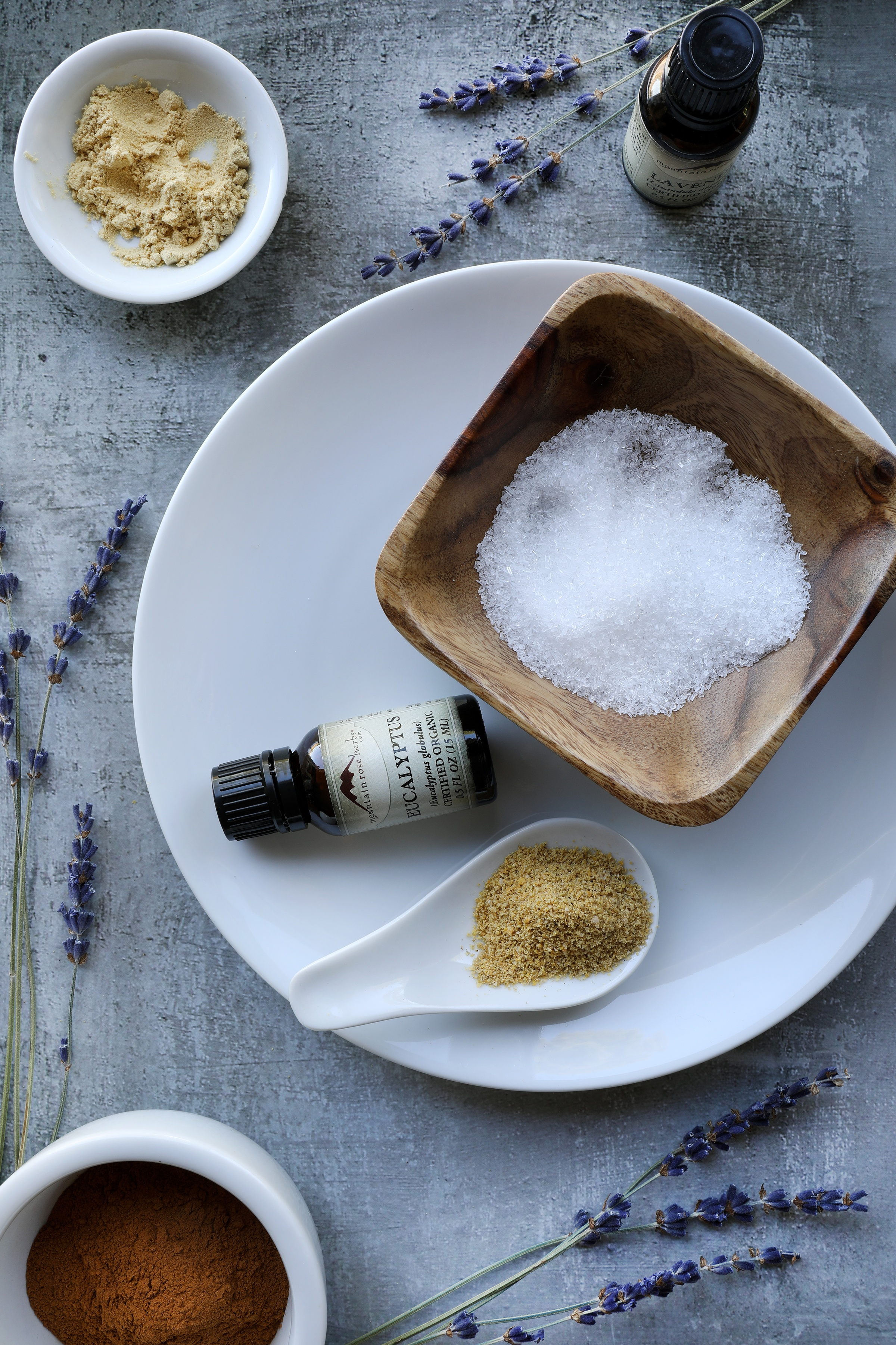 Ingredients for bath salts on rustic table with sprigs of lavender