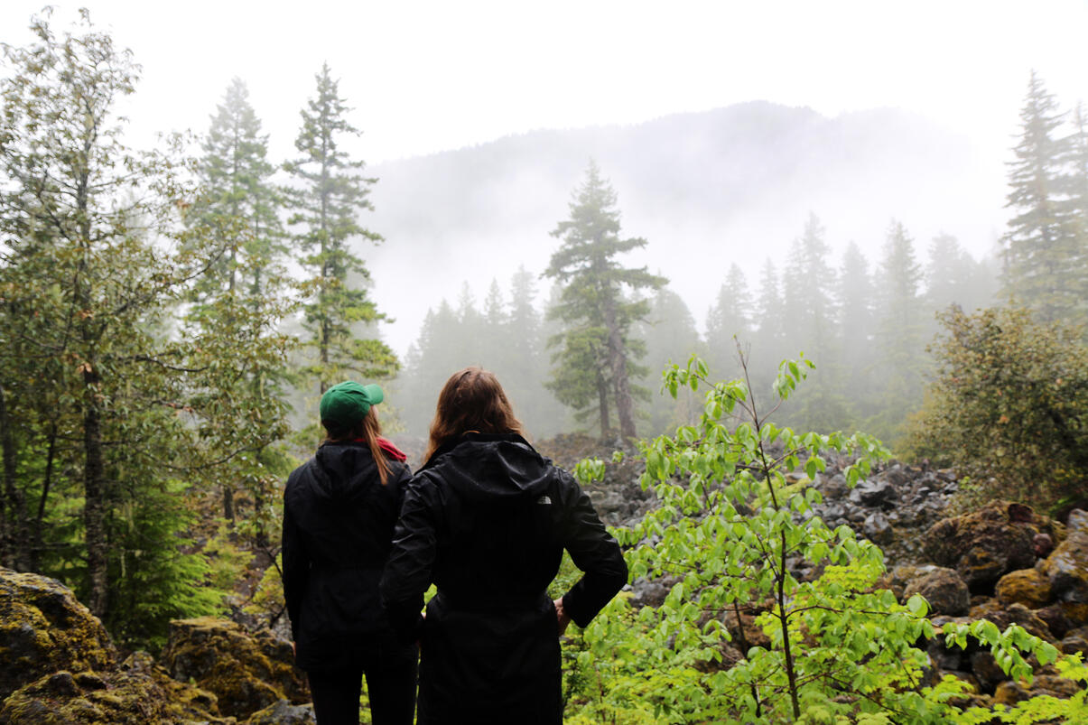 Two women pausing on a hike to look out upon a misty mountain view surrounded by evergreens.