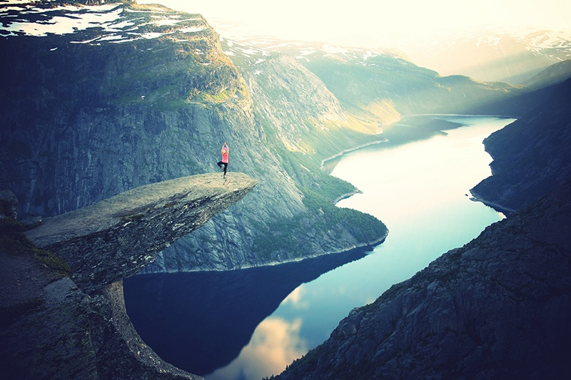 Woman doing yoga on cliff over a river