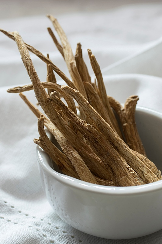Ginseng roots in a white porcelain bowl on a white linen tablecloth