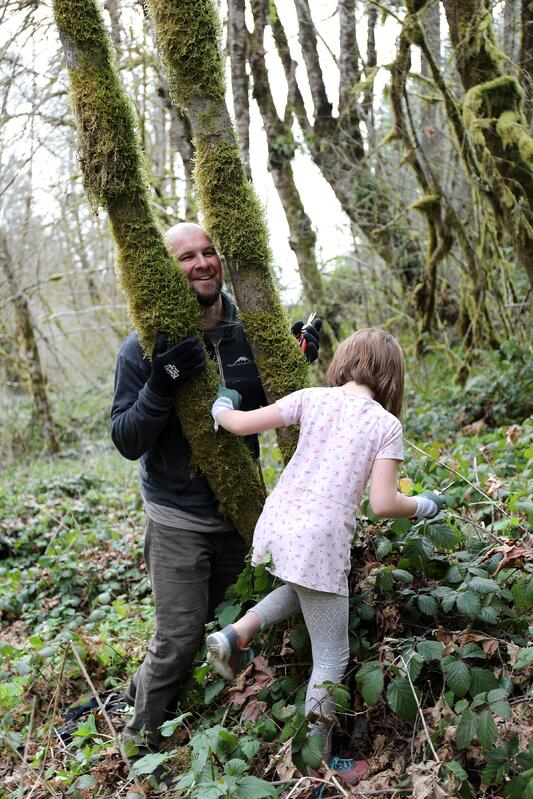 Father and daughter playing in wooded area