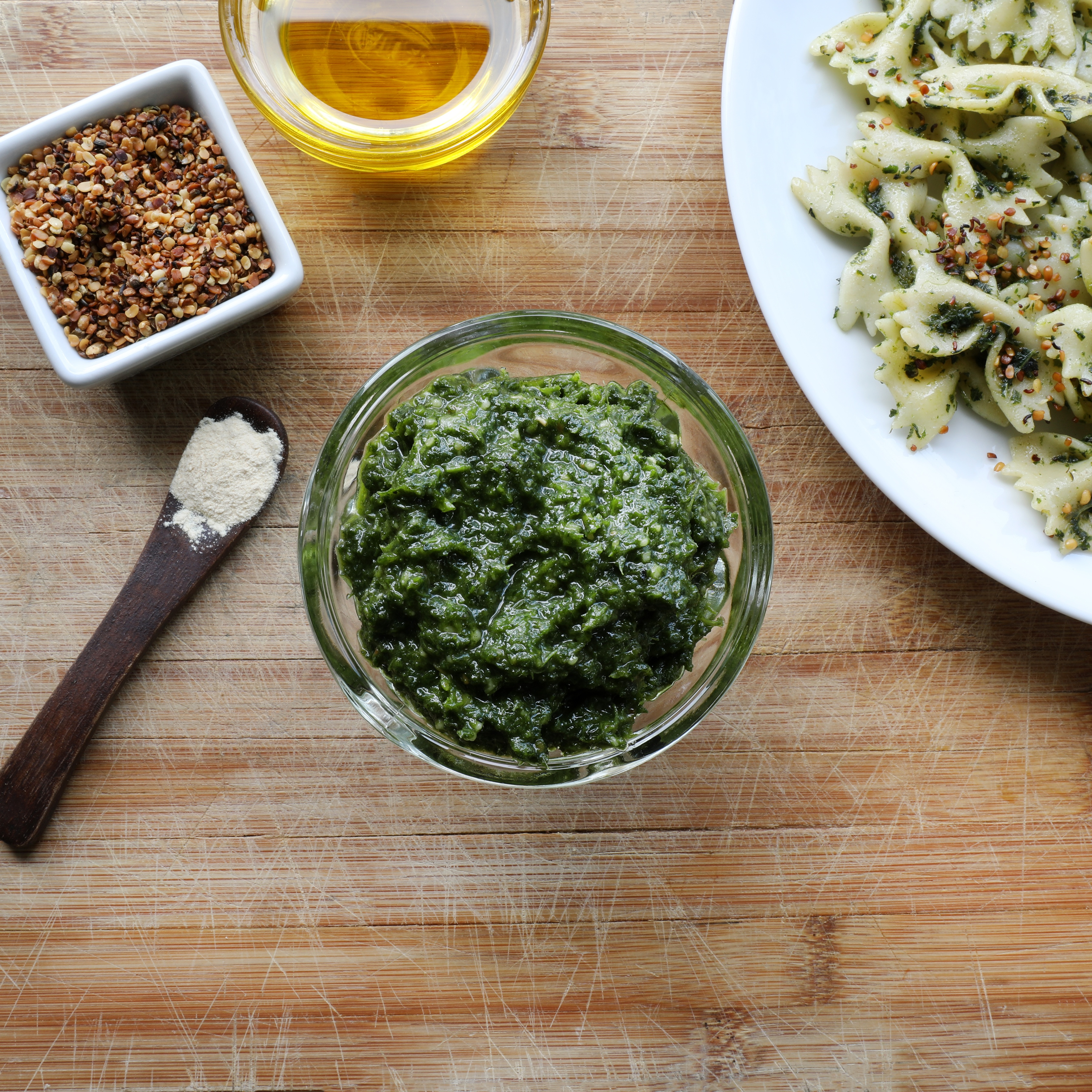 Nettle pesto in glass bowl near pasta and spoon with garlic powder, red pepper flakes, and olive oil