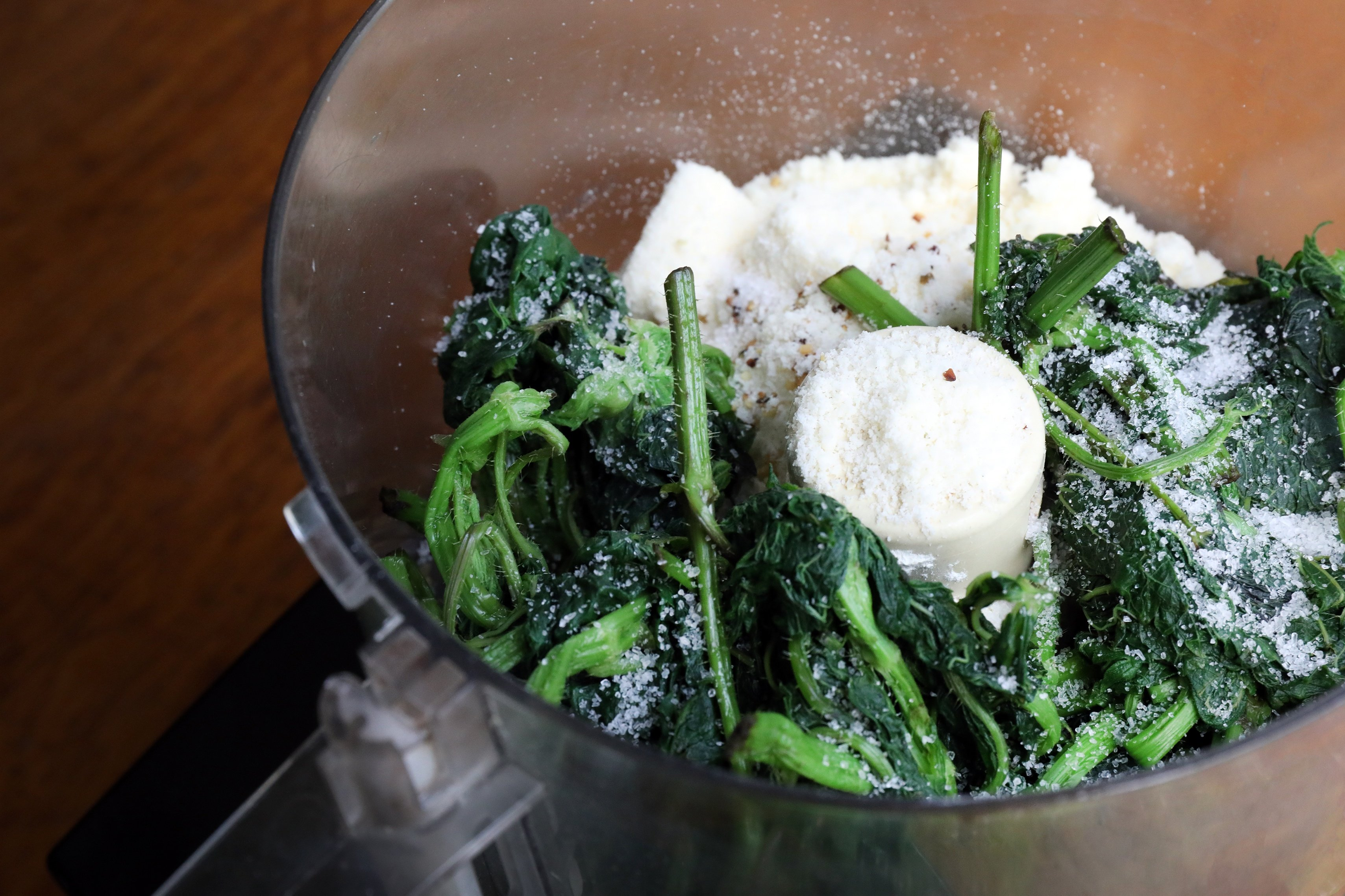 Blanched nettle leaves and other pesto ingredients in a food processor