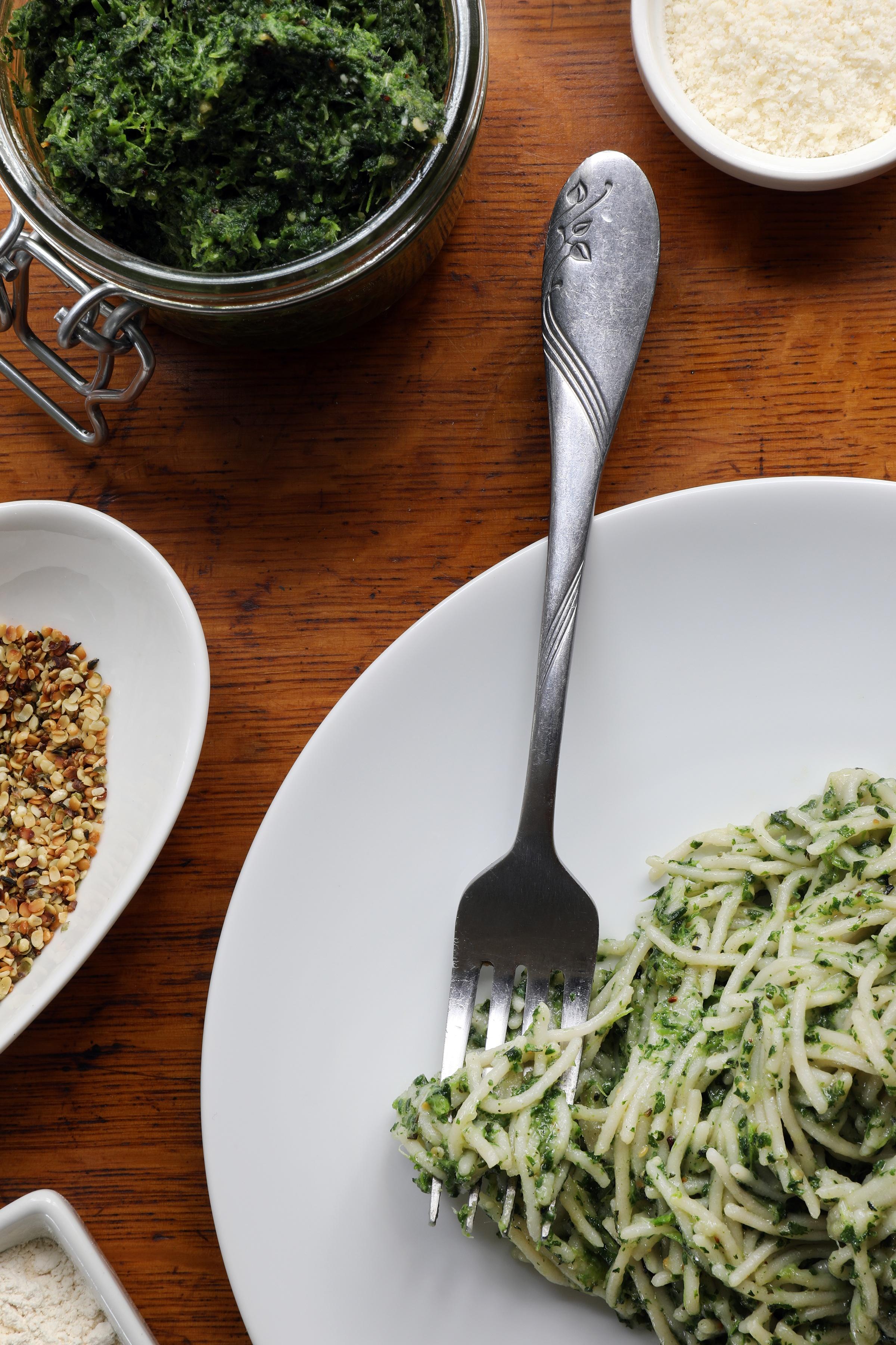 Fork on white plat sitting next to nettle pest pasta near nettle pest ingredients