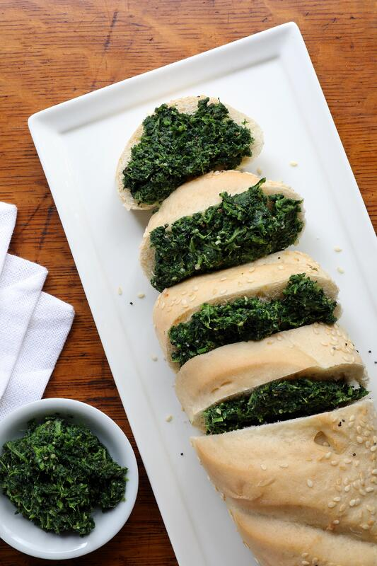 Platter with loaf of French bread sliced showing nettle pesto spread in between slices
