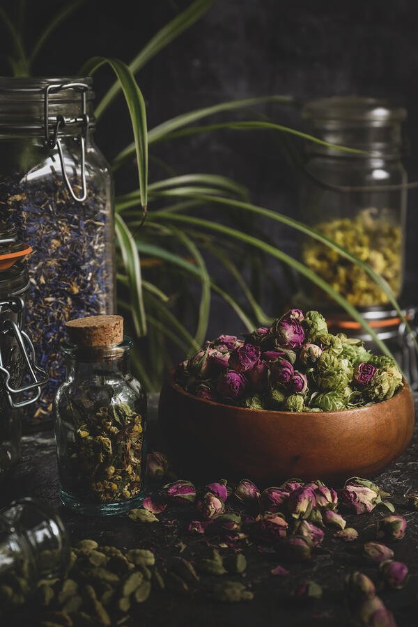 Beautiful herbs piled on a table and in jars.