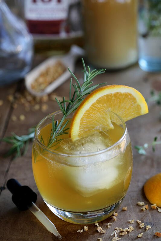 Small round glass with chilled orange color cocktail, fresh orange on rim and fresh rosemary sprig.