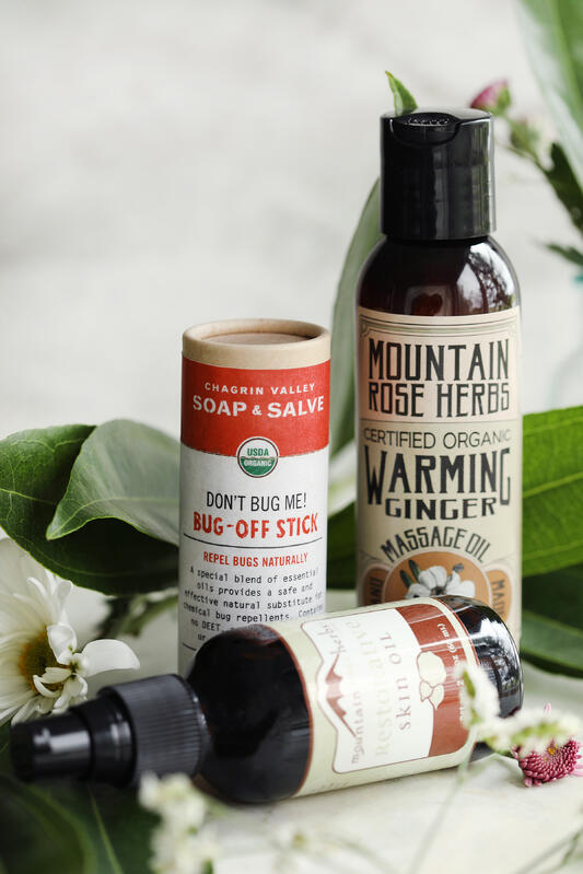 Gifts for an outdoorsy woman. Bug repellent, skin oil, and massage oils, all arranged among spring green foliage.