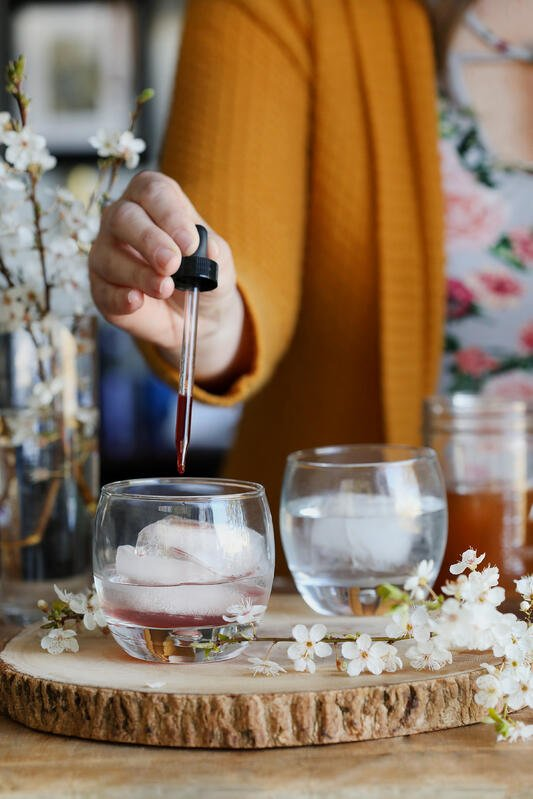 Using a dropper to add a finished herbal oxymel to beverages is a simple way to incorporate herbs into your wellness routine.