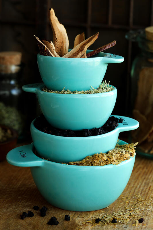 Bright sky blue measuring cups are full of herbal ingredients and stacked high. Reishi mushrooms, rosemary, and bilberries fill the measuring cups which are used to add ingredients in parts to herbal recipes.