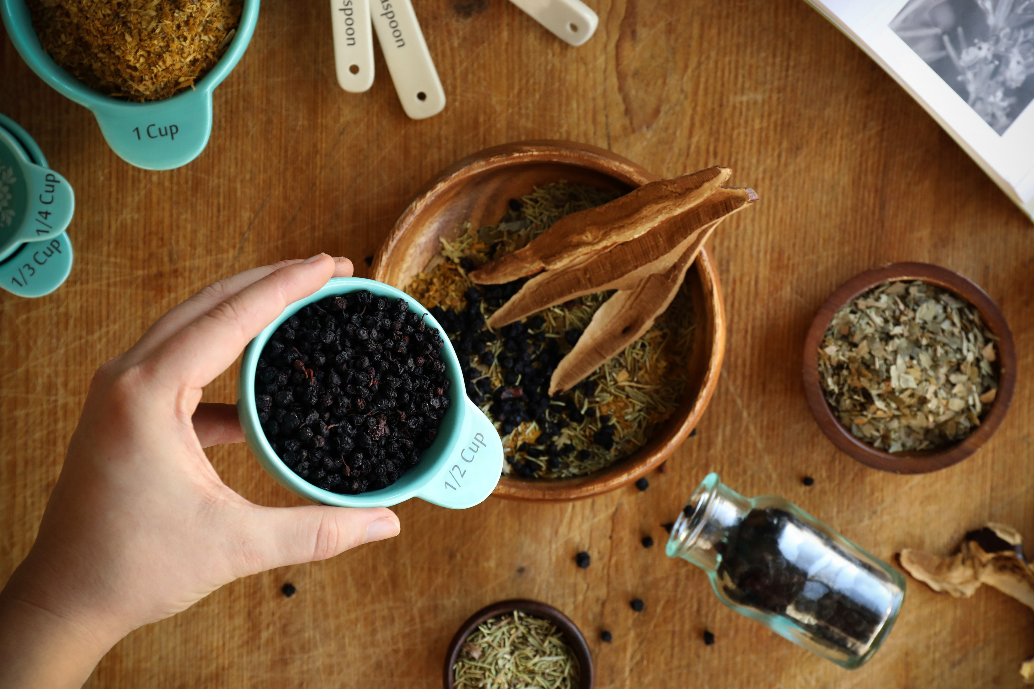 Using a half cup measuring vessel to pour organic dried bilberries into an herbal formula is simple when measuring in parts.