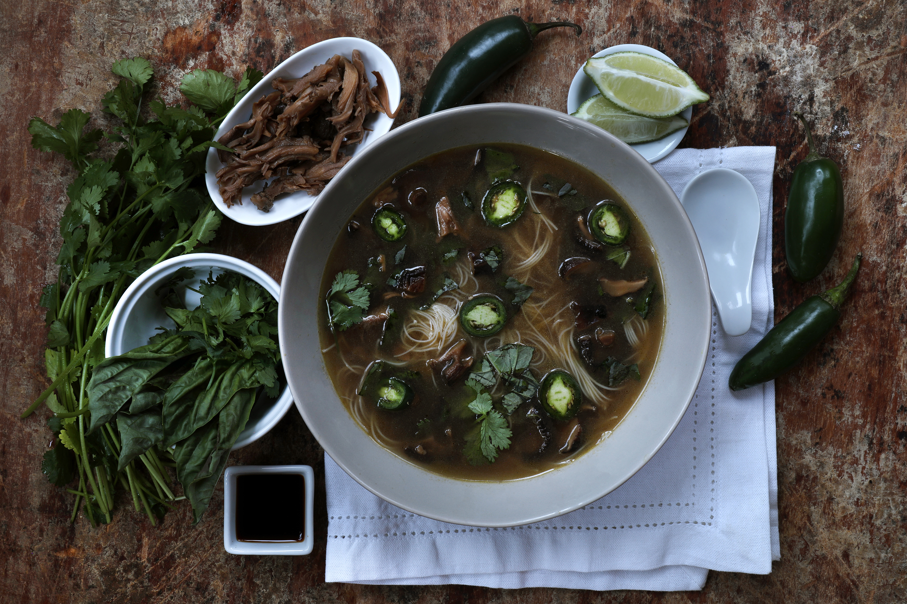 Bowl of pho soup with fresh ingredients around it.