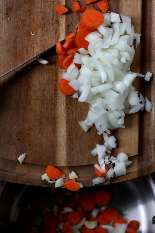 Wooden cutting board with knife actively dicing carrots, onions and garlic.