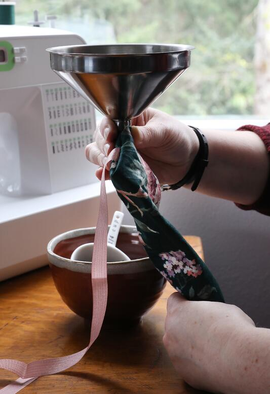 Hands using funnel to pour lavender and buckwheat into homemade eye pillow